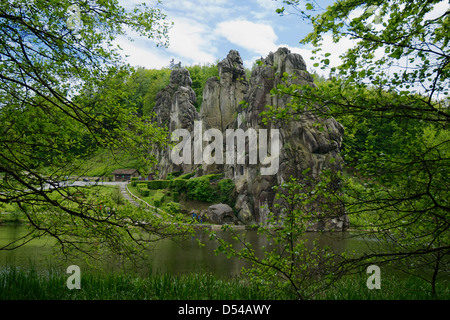 Wide view of Externsteine rock formation with tree branches in the foreground. - Stock Photo