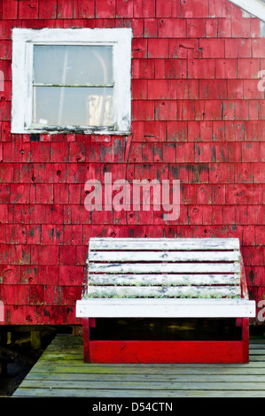 An empty white bench sits next to a lobster shack in Maine. - Stock Photo