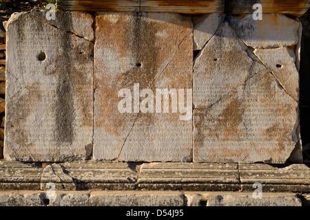 Greek inscription on stone blocks on Curetes street of ancient Ephesus Turkey - Stock Photo