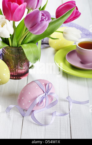 Pink, violet and white tulips in a glass vase with easter eggs on wooden background - Stock Photo