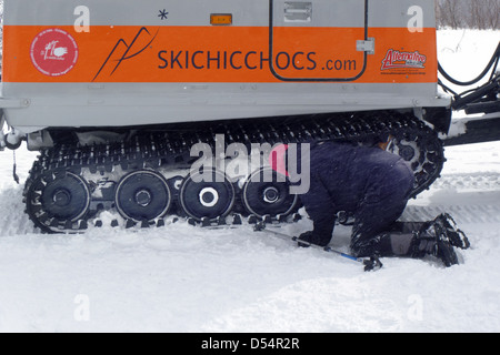 Clearing snow from the tread of a snow cat, in the chic choc mountains in Gaspesie Quebec Canada - Stock Photo