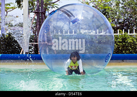 Youngster walking on water in a floating balloon. - Stock Photo