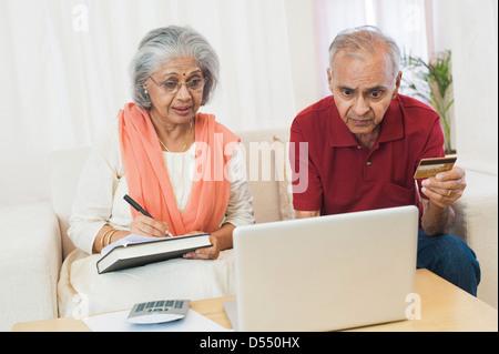 Senior couple checking bills on a laptop - Stock Photo