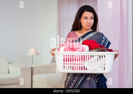Woman carrying a laundry basket - Stock Photo