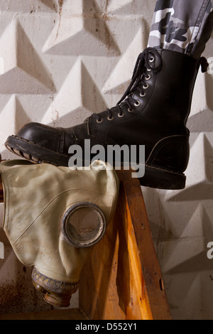black army boots standing on gas mask in an abandoned basement - Stock Photo