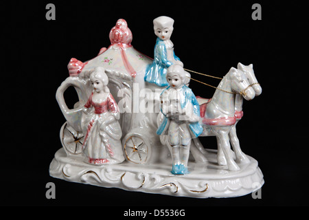 ceramic figurine in the form of carriage drawn by two horses and three people on a black background - Stock Photo