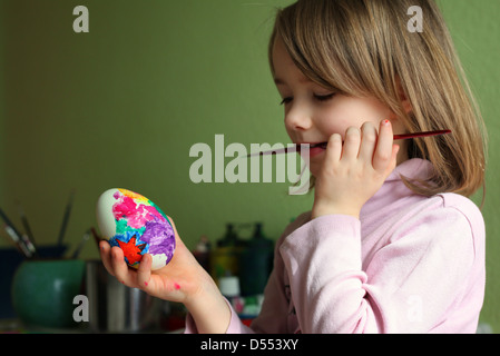A happy young German girl painting eggs at home for Easter. Leipzig, Germany, Europe. - Stock Photo