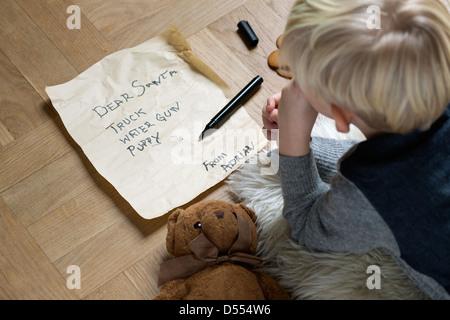 Boy writing Christmas list for Santa
