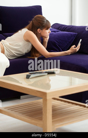Woman taking picture of herself on sofa - Stock Photo
