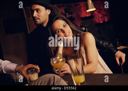 Smiling pretty woman at the bar enjoying with her friends - Stock Photo