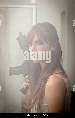 Woman holding machine gun at window - Stock Photo