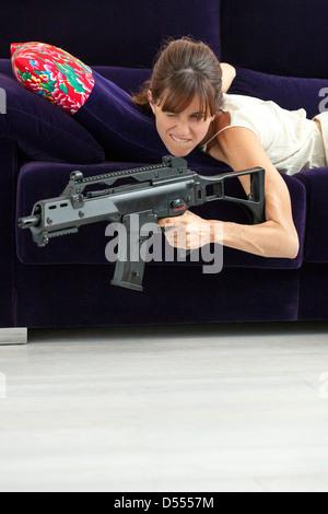 Woman shooting machine gun on sofa - Stock Photo