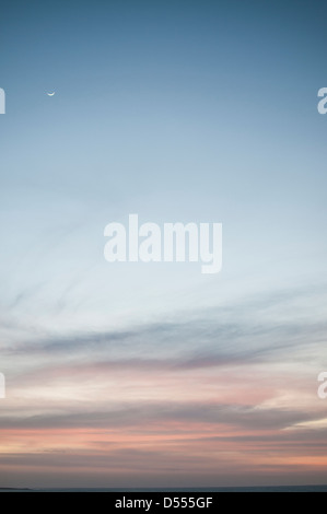 Moon rising over colorful sky - Stock Photo