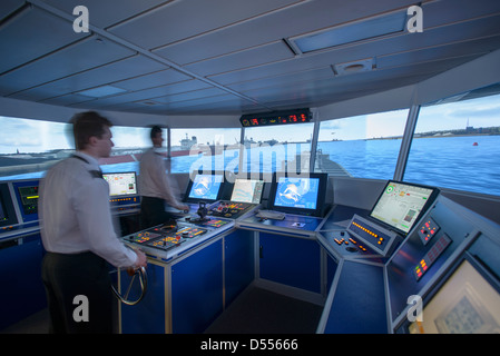 Personnel working on ships bridge - Stock Photo
