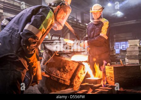 Workers pouring molten metal in foundry - Stock Photo