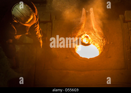 Worker stirring molten metal in foundry - Stock Photo