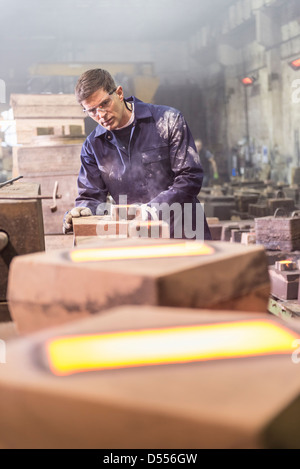 Worker examining moulds in metal foundry - Stock Photo