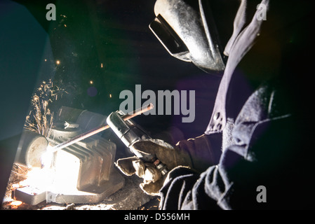 Worker welding metal in foundry - Stock Photo