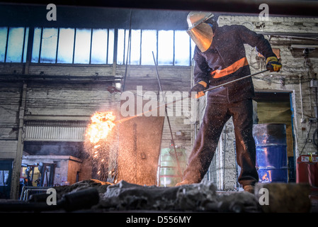 Worker cleaning metal in foundry - Stock Photo