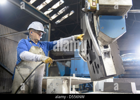 Worker cleaning mould in metal foundry - Stock Photo