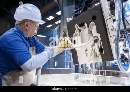 Worker coating mould in metal foundry - Stock Photo