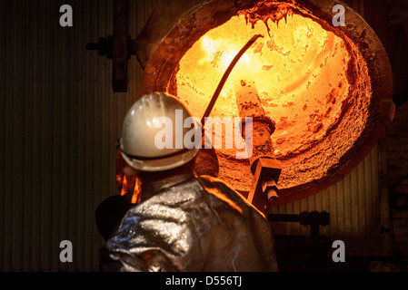 Workers cleaning metal flask in factory - Stock Photo