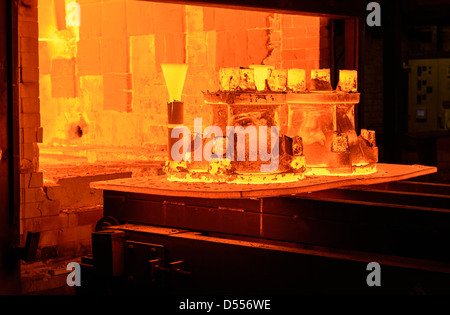 Metal casings glowing in foundry - Stock Photo