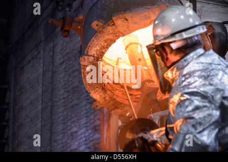 Worker cleaning metal flask in foundry - Stock Photo