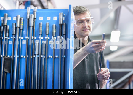 Worker inspecting drill rods in factory - Stock Photo