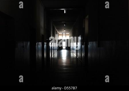 Light shining from door in dark hallway - Stock Photo