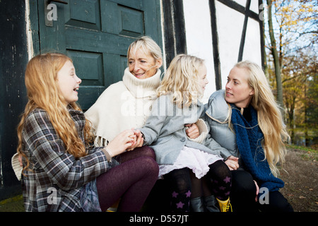 Mother and daughters sitting outdoors - Stock Photo