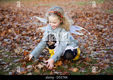 Girl in fairy wings playing in leaves - Stock Photo