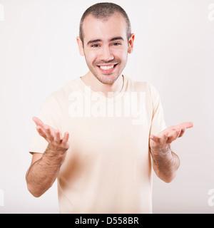 Happy smiling man on shirt presenting and showing something on white background - Stock Photo