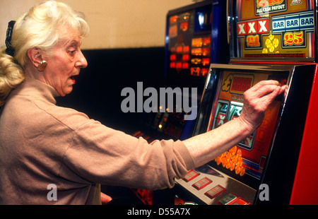 Elderly woman playing slot machine in bingo hall, Hounslow, Middlesex, UK. - Stock Photo