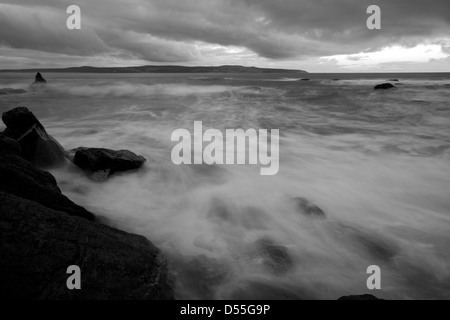 Waves washing around the rocks at Godrevy in Cornwall - Stock Photo