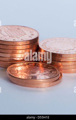 Close-up of new shiny coppers or pennies (British unit of currency 1p coins) in 3 small piles, grand total of money - Stock Photo