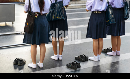 Schoolgirls at Ganesha-shrine in front of CentralWorld - shopping mall in Bangkok, Thailand, Asia - Stock Photo