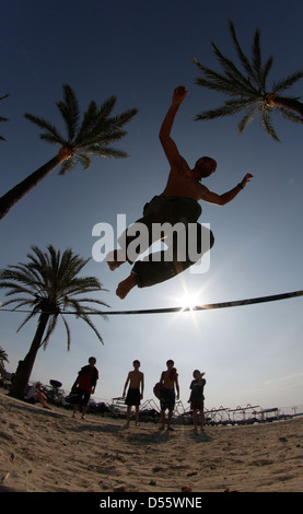 A young man practice slackline on the beach. Slacklining is a practice in balance that typically uses nylon or polyester - Stock Photo
