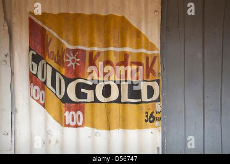 Painting on corrugated tin advertising Kodak gold film, Kenya. - Stock Photo