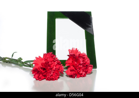 green photo frame with a mourning black tape and red carnations on a light background - Stock Photo