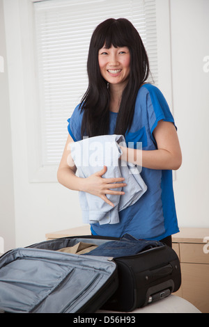 Chinese woman packing suitcase in bedroom