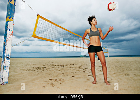 Mixed race woman playing with volleyball on beach - Stock Photo