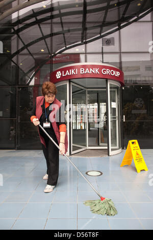 Nicosia, Cyprus. 26th March 2013.  Picture shows Tasoula Christadoulou continuing as normal cleaning the forecourt - Stock Photo