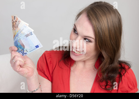 Young woman holding euro notes in hand and looking exited, might be borrowed cash money from parent. - Stock Photo