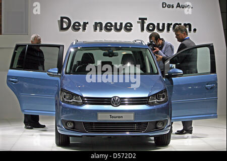 Visitors check out the new Volkswagen Touran at a world premiere at the Auto Mobil International (AMI) car show - Stock Photo