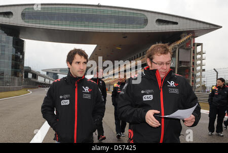German Formula One driver Timo Glock of Virgin Racing (L) and a team member walk over the Shanghai International - Stock Photo