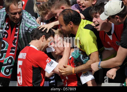 Hanover's Mike Hanke (C) and Mario Eggimann (L) cheer after Hanke's goal to the score 4-0 during German Bundesliga - Stock Photo