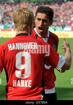 Hanover's Mike Hanke (L) and Karim Haggui cheer after Haggui's goal to the score 1-0 during German Bundesliga match - Stock Photo