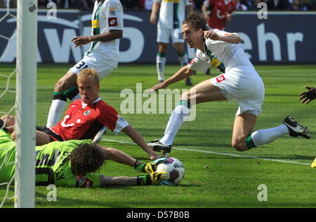 Hanover's Mike Hanke (L) lays in the penalty box next to Gladbach's goalkeeper Logan Bailly and his team mate Roel - Stock Photo