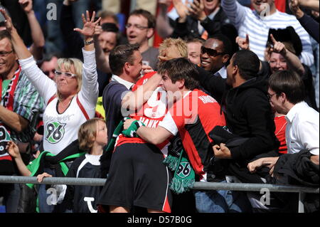 Hanover's Mike Hanke (hidden, C) cheers with Hanover fans about his goal to the score 4-0 during German Bundesliga - Stock Photo